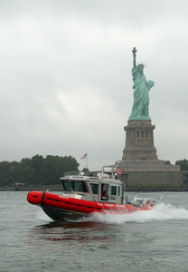 A U.s. Coast Guard Boat Patrols The In New York Harbor By The Statue Of Liberty As Part Of Their Homeland Security Mission Image