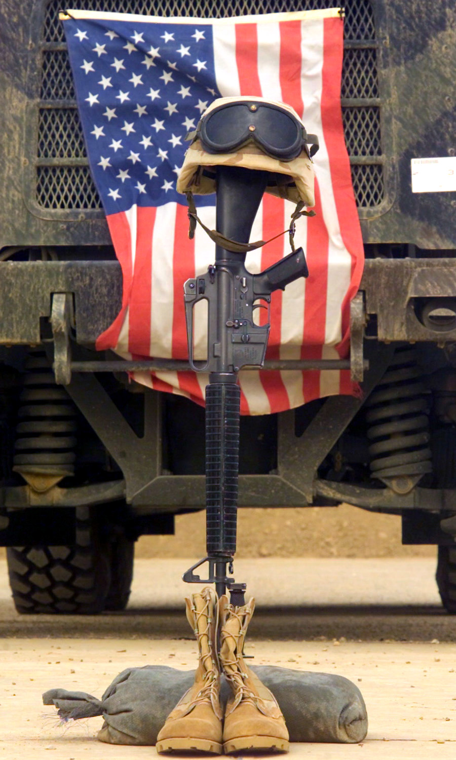 An M16 A2 Service Rifle A Pair Of Boots And A Helmet