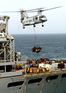 A Ch-46 Sea Knight Helicopter Delivers Supplies From The Fast Combat Support Ship Uss Bridge (aoe 10) To The Aircraft Carrier Uss Constellation (cv 64) During An Underway Replenishment Image