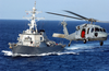 An Mh-60s Knighthawk Helicopter Flies By The Guided Missile Destroyer Uss John S. Mccain (ddg 56) Image