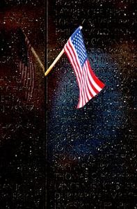 A Small Flag Reflects Against Names Inscribed On The Vietnam Veterans Memorial. Image