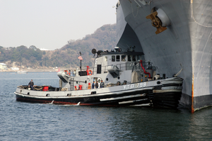 A Large Harbor Tug Uss Opelika (ytb 798) Assists Amphibious Command And Control Ship Uss Blue Ridge (lcc 19) To Its Berth After A Scheduled Deployment In The Western Pacific Image