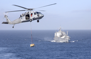 Sh-60 Approaches The Ship S Flight Deck During An Early Morning Refueling At Sea Image