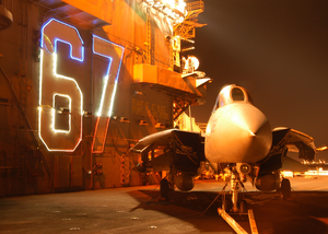 An F-14b Tomcat Assigned To The Jolly Rogers Of Fighter Squadron One Zero Three (vf-103) Sits In Front Of The Lighted Island Hull Number Aboard The Aircraft Carrier Uss John F. Kennedy (cv 67). Image