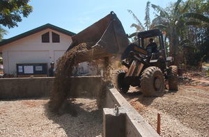 A Front Loader Assigned To The  Club And Spades  Of Naval Mobile Construction Battalion Two Five (nmcb 25), Pours Earth To Be Used In The Building Of A Foundation At The Manuel Memorial Elementary School. Image