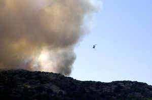 An Italian Helicopter Assists In U.s. Navy Fire Fighting Efforts On The Island Of Santo Stefano Image