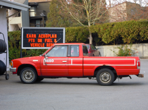 Old Red Nissan Pickup Truck At Gas Station Image