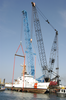 Two Cranes Work In Tandem From A Barge To Lower A U.s. Coast Guard (uscg) Patrol Boat Into The Water. Image