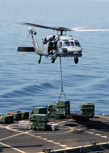 An Mh-60s Knight Hawk Delivers A Crate Of Ordnance To The Military Sea Lift Command, Ammunitions Ship Usns Kiska (t-ae 35) During A Weapons Transfer From The Uss Abraham Lincoln (cvn 72) Image