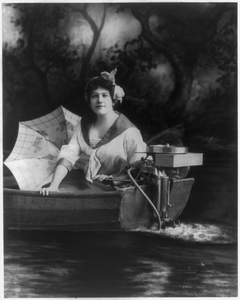 Young Woman Posed With An Evinrude Outboard Motor Image