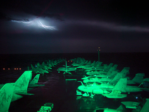 Lightning Fills The Horizon, And Lights Up The Flight Deck And Air Wing Aircraft Parked On The Ship S Forward Elevator And Bow. Image