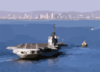 A Tugboat Tows The Decommissioned Aircraft Carrier Midway Into San Diego Bay. Clip Art