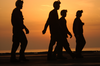 Crewmembers Walk Across The Ship S Flight Deck Before The Sun Sets Over The Arabian Sea. Image