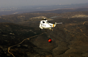 An Uh-3h Sea King Helicopter Assigned To The Golden Gaters Of Helicopter Combat Support Squadron Eight Five (hc-85) Strapped With A Bambi Bucket Full Of Water Participates In A Training And Certification Flight Image