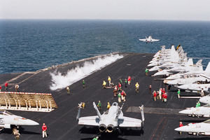 An F/a-18c  Hornet  Is Launched From The Ship S Flight Deck While Another Stands By. Image