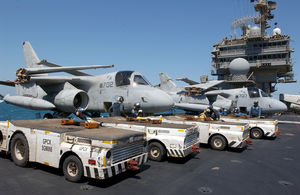 Tow Tractors Are Positioned On The Starboard Side Of The Flight Deck In Preparation For Aircraft Movement After The Conclusion Of Daily Flight Operations Aboard The Aircraft Carrier Uss Kitty Hawk (cv 63) Image