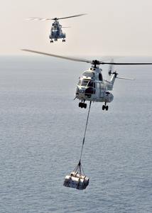 An Sa-330 Puma Helicopter Carries Supplies From Military Sealift Command Ship, Usns Saturn (tafs 10) Over To The Aircraft Carrier Uss Enterprise (cvn 65) During A Replenishment At Sea (ras) Image