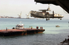 An E-2c  Hawkeye  Is Hoisted And Lowered Onto A Barge In Bahrain Image