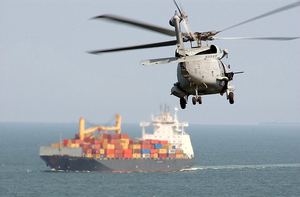 An Sh-60f Seahawk  Heads Off Toward A Group Three Merchant Vessel Surface Image
