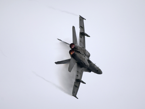 An F/a-18 Hornet Performs A High-speed Turn Near The Aircraft Carrier Uss John C. Stennis (cvn 74) Image