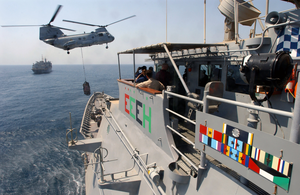 A Ch-46 Sea Knight Helicopter Attached To The Fast Combat Support Ship Uss Bridge (aoe 10), Transfers Supplies To The Guided Missile Cruiser Uss Chosin (cg 65) During A Vertical Replenishment, (vertrep) Image