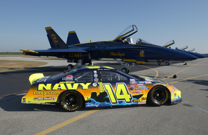 The Navy Sponsored Chevrolet Monte Carlo Busch Series Race, Show Car Is Parked On The Tarmac Near F/a-18 Hornets Assigned To The Navy S Flight Demonstration Team, The Blue Angels, At Sherman Field Onboard Nas Pensacola. Image
