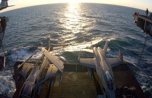 An Ea-6b And An F/a-18c Are Raised To The Flight Deck On One Of Four Aircraft Elevators Aboard Uss Kitty Hawk (cv 63) Image