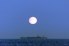 A Full Moon Illuminates The Nuclear Aircraft Carrier Carl Vinson. Image