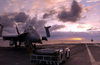 The Sun Rises Behind An F/a-18  Hornet  Strike Fighter Aircraft Parked And Secured On The Ship S Flight Deck. Image