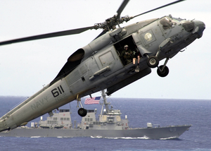 An Sh-60 Seahawk Helicopter Slows Down To Lower It Image