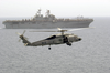 A Sh-60 Seahawk Helicopter Comes In For A Landing On The Flight Deck Of Uss Nimitz (cvn 68), While The Amphibious Assault Ship Uss Iwo Jima (lhd 7) Cruises Alongside Image