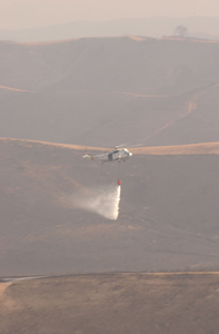 A Sea King Helicopter (uh-3h) Assigned To The  Golden Gators  Of Reserve Helicopter Combat Support Squadron Eighty Five (hc-85) Uses A  Bambi  Bucket To Conduct Water Drops On Brush Fires Image