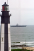 Precommissioning Unit (pcu) Ronald Reagan (cvn 76) Passes A Lighthouse Located At Fort Story Army Base Image