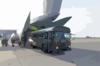 A Transport Bus From The U.s. Navy S Fleet Hospital Eight Backs Into The Tail Of A Waiting Air Force C-5 Galaxy Medical Evacuation (medevac) Plane. Clip Art